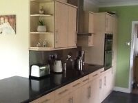 Beech kitchen units with black laminate worktop including appliances