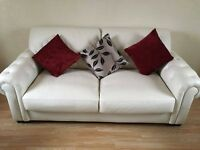 Cream leather sofa and two arm chairs.