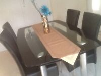 Black Glass dining Table and chairs plus some wicker furniture