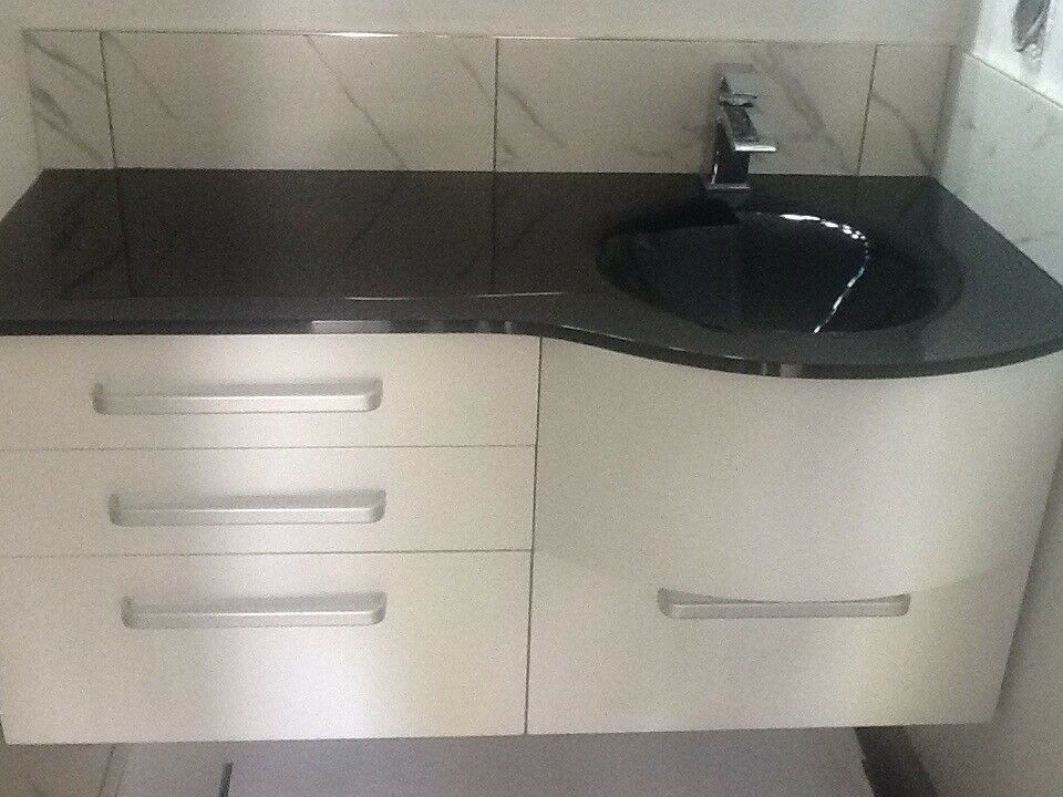 Modern white wall hung 1100cm vanity unit with black glass counter top and left hand basin.