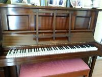 Upright piano and double piano stool in excellent condition. Wires are overstrung on a metal frame.