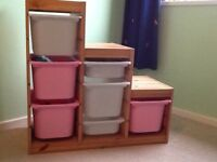Trofast wooden storage with white and pink plastic baskets