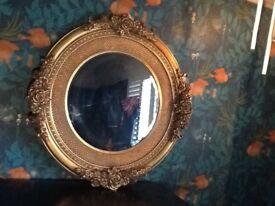 decorative antique gold round mirror with carved flowers around the edge.