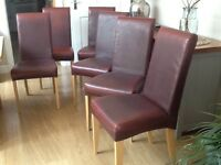 Set of six red faux leather dining room chairs.
