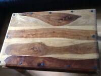 Solid wood coffee table with black metal hinge detailing. 90cm x60cm x45cm.