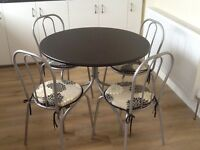 Black round table and 4 chairs with chair pad