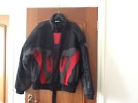 Motor cycle jacket with reinforcing at elbows.
