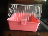 Pink pet cage for inside or to carry your pets wit door opening was used to keep a rabbit inside