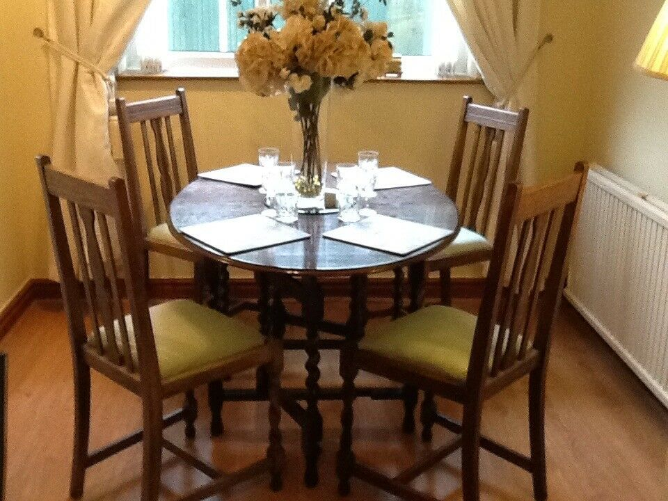 Oval dark oak drop leaf dining table, with barley twist legs and 4 chairs (green seat covers).