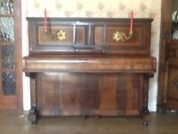 Piano,uprigh. Attractively decorated with inlay and brass candle holders