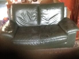 Two seater green leather Natuzzi sofa.