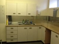 Small kitchen includes stainless steel splash back