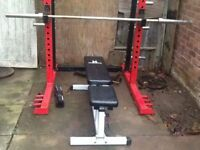 squat rack with olympic barbell and 2 x 25kg weight plates and olympic weight bench