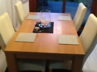 Wooden dining table and 4 faux leather chairs.