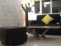 Black leather and chenille 2 seater sofa and footstool