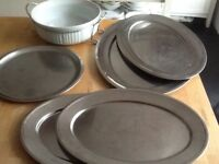 5 stainless steel serving platters with large ceramic dish and stand
