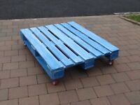 Blue shabby chic pallet coffee table with orange wheels