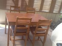 Pine dining table and 4 chairs with cushions.