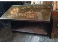 Caved wooden coffee table with glass on top
