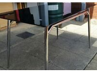black glass dining table, on chrome metal frame legs. 120cm x 75cm. In used condition.