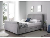 Grey upholstered king-sized sleigh bed