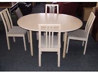 Round white dining table (extends) with four chairs.