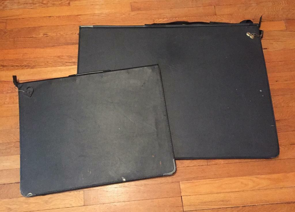 Two well used black portfolio folders. A1 and A2. The A2 folder has a ring binder closure.