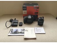 Sony A57 DSLR camera with 18-55mm lens and accessories