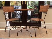 Bistro table and two chairs for indoor outside use; wrought iron and bamboo cane dining set