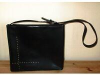 Stylish black handbag with brown cross detailing
