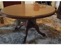 Lovely old mahogany wood oval pedestal table with a thick glass top covering wood