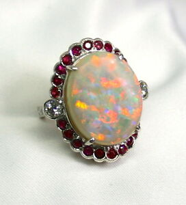 LADIES SOLID OPAL 18K WHITE GOLD RING SURROUNDED BY RUBIES AND DIAMONDS