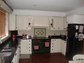Hand painted kitchen units with black granite worktop