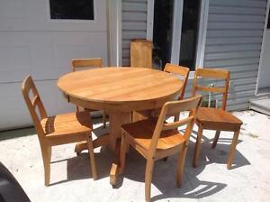Table ronde antique avec rallonge et chaises.