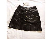 Woman's black leather a-line skirt with gold buttons down front and pockets