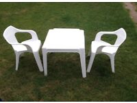 White plastic table and two chairs set. Blue single plastic chair.