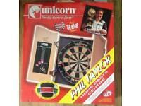 Brand new dart board in wooden cabinet.