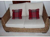 Rattan sofa and chair set with neutral cream cushions