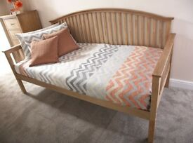 A 3ft single day bed, oak finish, new, without mattress.
