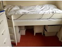 White wooden single cabin bed with attached ladder