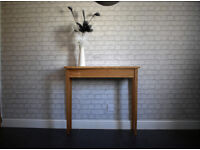 A solid oak bespoke console table with a live edge slab top.