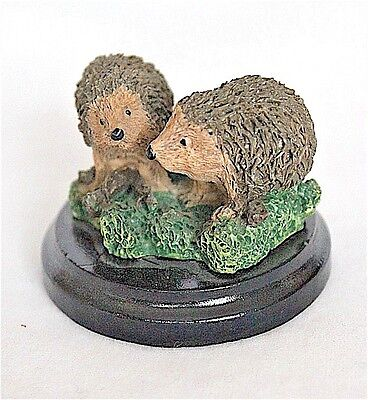TWO COLLECTABLE HEDGEHOGS ON A WOODEN PLINTH