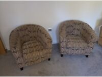Pair of matching bucket-chairs with brown covers.
