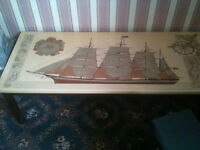 COFFEE TABLE Printed picture of ship (some wear and tear) Ceramic top Any questions welcome