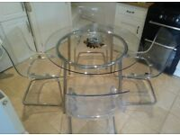 Glass-top dining table with four chairs