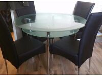 Round glass dining table and 4 black chairs (Harveys boat range)