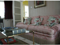 Pink floral suite, two arm chairs and three seater sofa