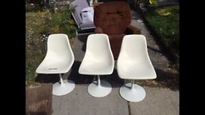 3 white plastic chairs with metal base.