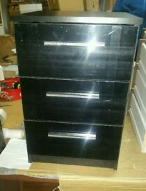A brand new black finish 3 drawer bedside table with sparking handles .