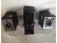 Three box brownie cameras and cases.